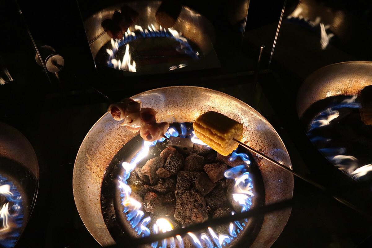 Das Foto ziegt Mais und Pflaumen im Speckmantel, die überm Feuer der Knüppelknifte gegart werden