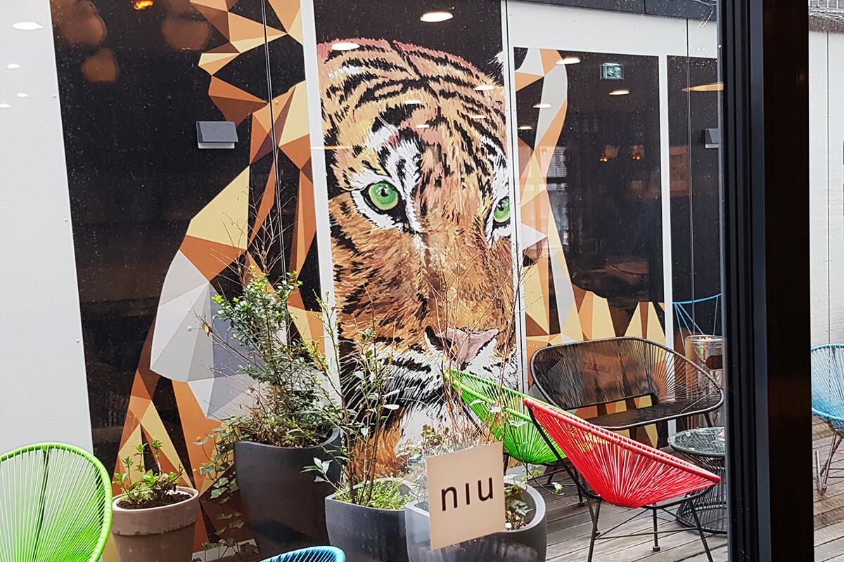 Das Foto zeigt eine tierische Wandmalerei in Form eines Tiger im Hinterhof des niu Cobbles in Essen