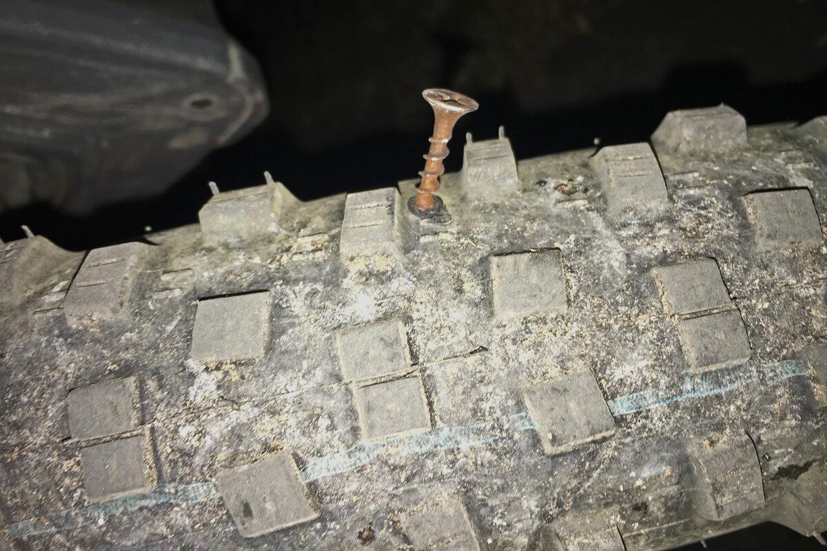 Das Foto zeigt einen rostigen Nagel im Fahrradreifen