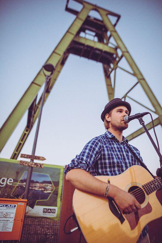 Das Bild zeigt einen Künstler mit Gitarre vor einem Fördergerüst.