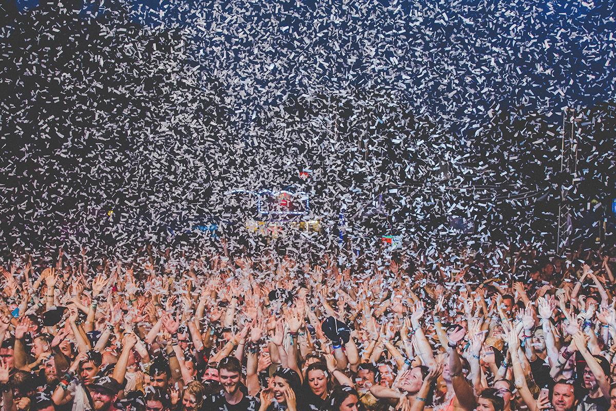 Das Bild zeigt eine feiernde Menge im Konfettiregen