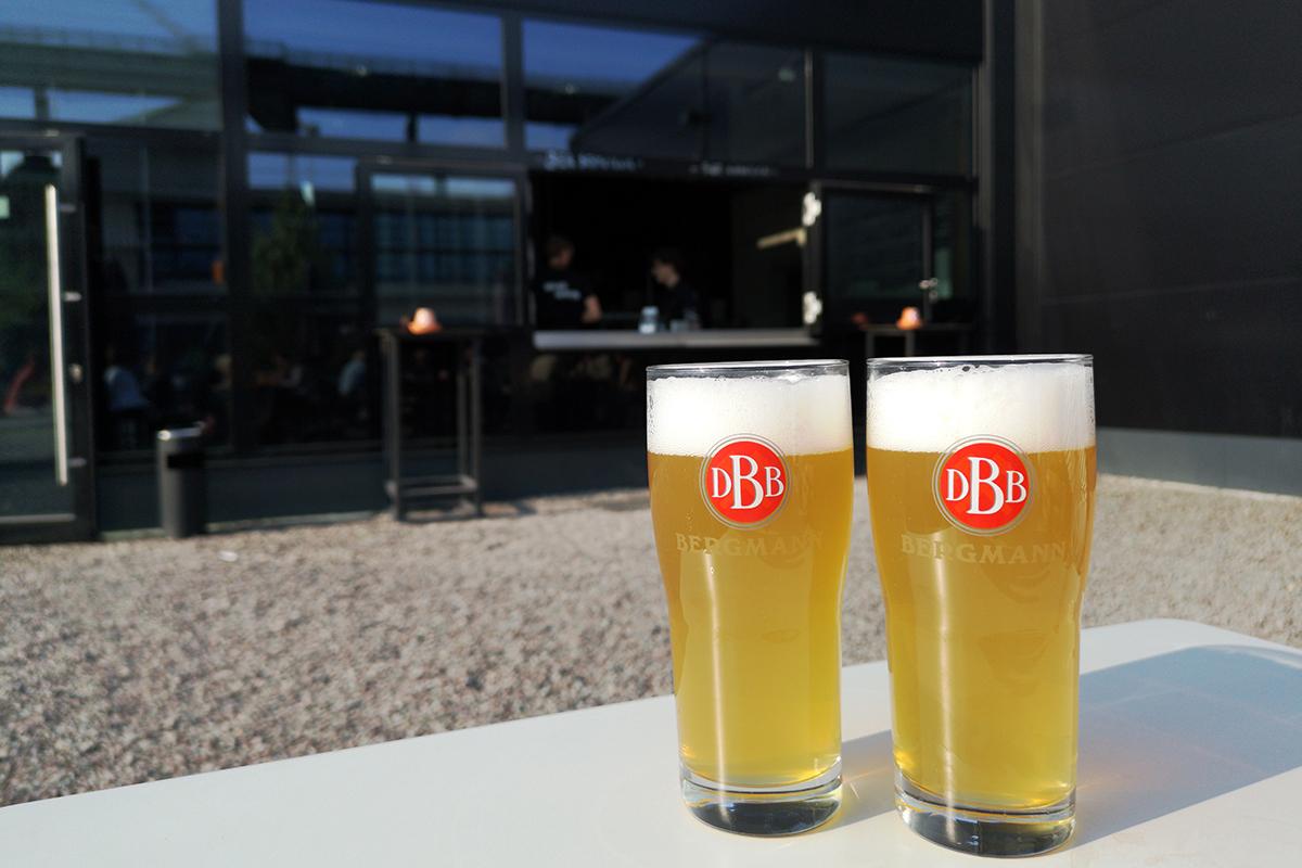 Zwei Gläser mit frisch Gezapftem Bier vor der Kulisse der Bergmann Brauerei