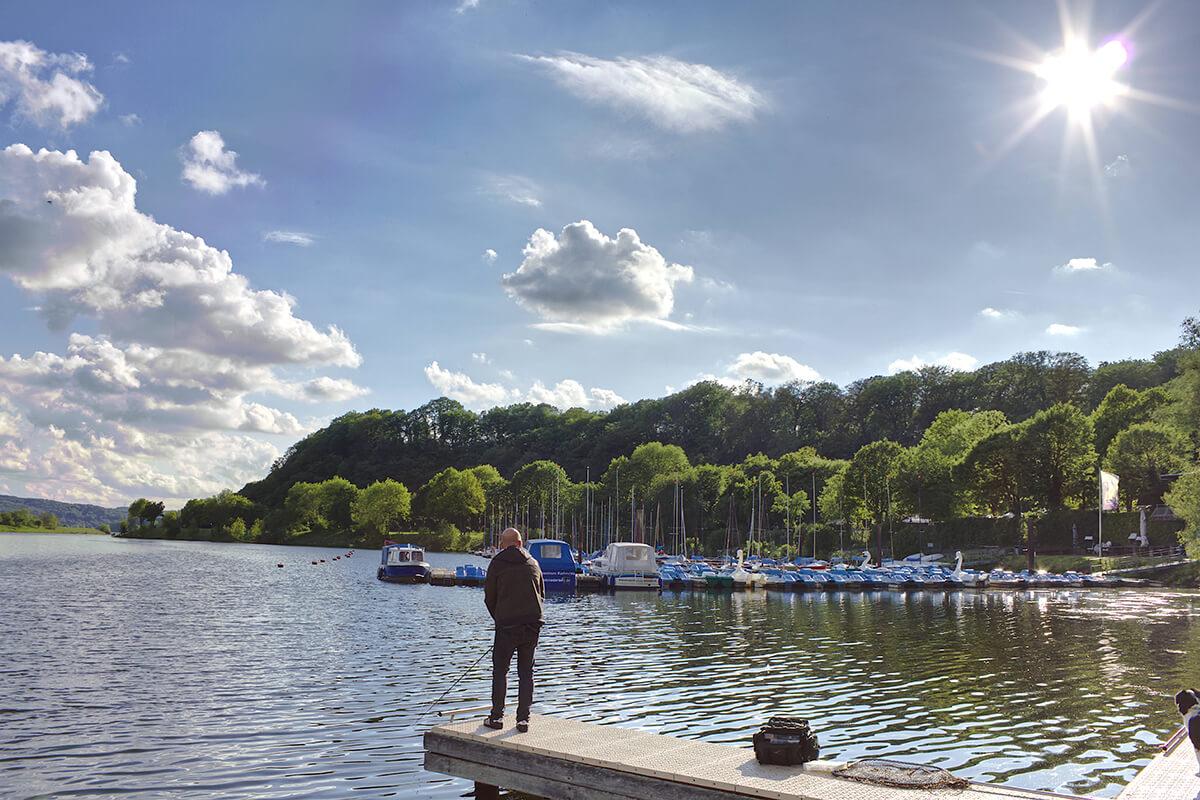Das Foto zeigt einen Angler am Kemnader See in Bochum, der sich als Ausflugsziel bestens für einen Kurzurlraub mit Hund im Ruhrgebiet eignet