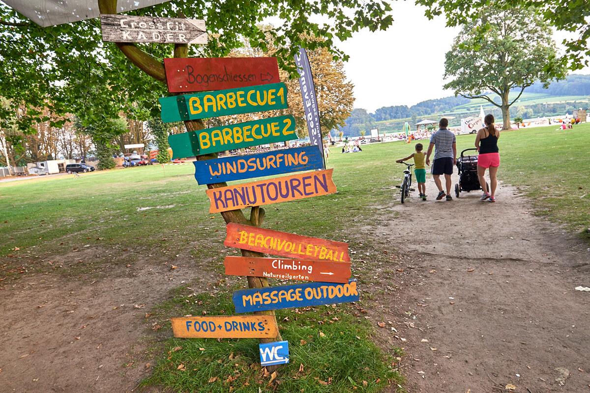 Das Foto zeigt Holztafeln, die die Aktivitäten des Seaside Beach Baldeney am Baldeneysee in Essen, einem der vielen Beach Clubs im Ruhrgebiet, anzeigen