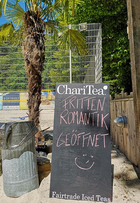 Das Foto zeigt eine Tafel mit der Aufschrift Fritten Romantik im StrandDeck Kemnade am Kemnader See, einem der vielen Beach Clubs im Ruhrgebiet