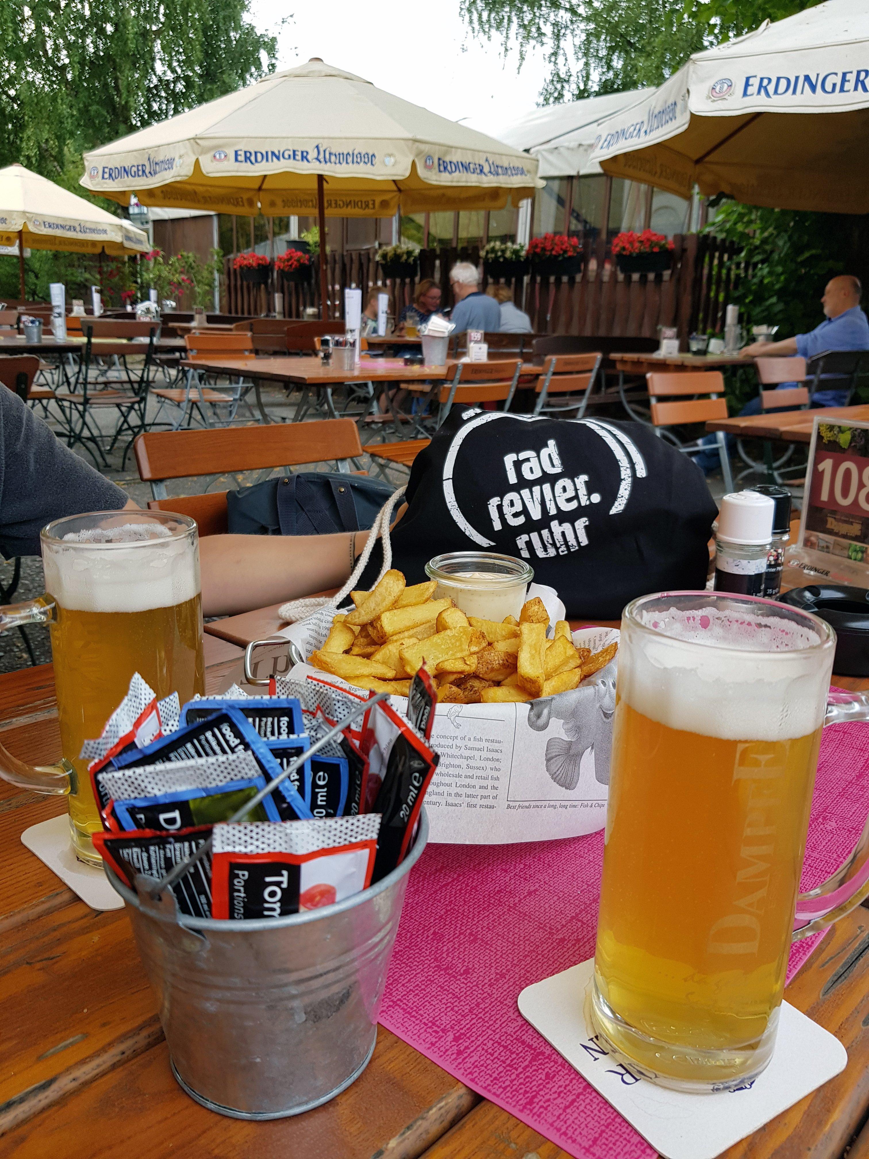 Das Bild zeigt zwei Gläser Bier und eine Portion Pommes