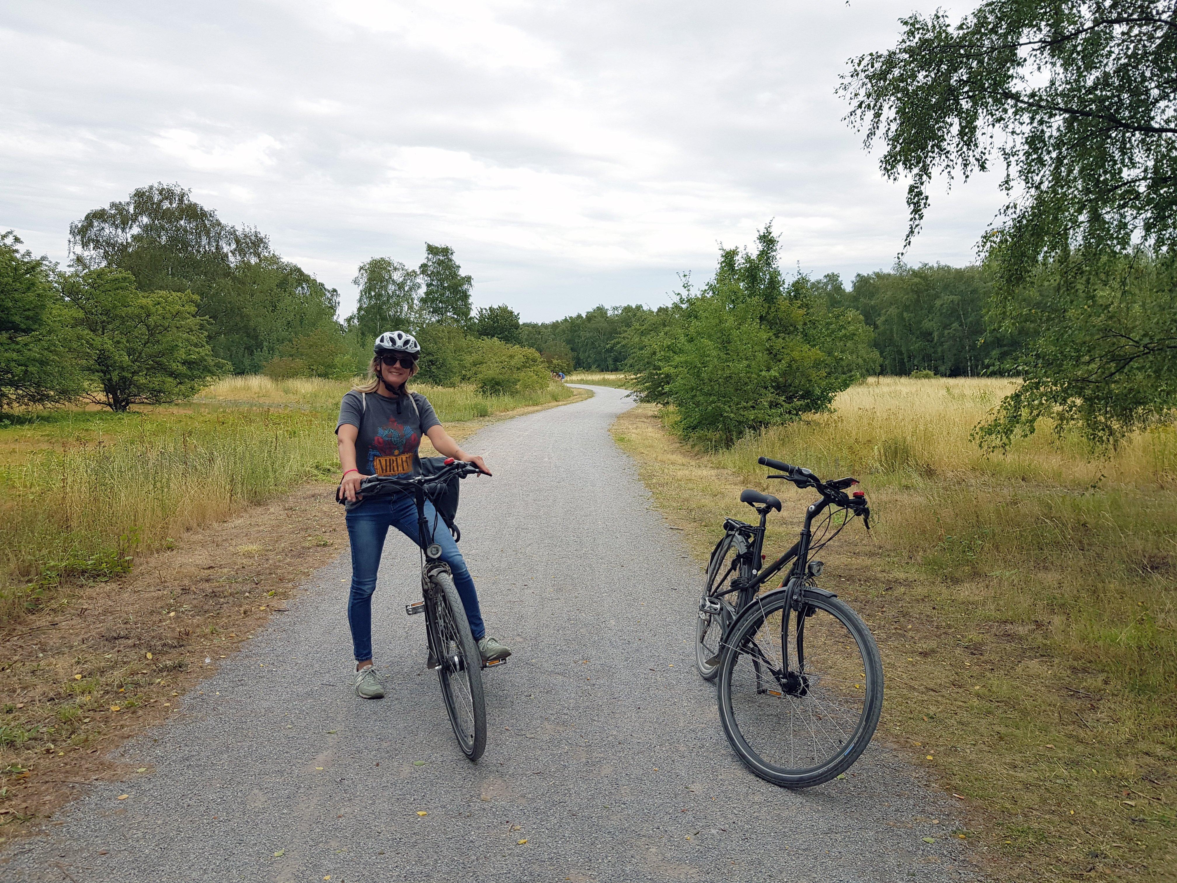 Das Bild zeigt eine Radlerin im Gleispark Frintrop mit Industrienatur