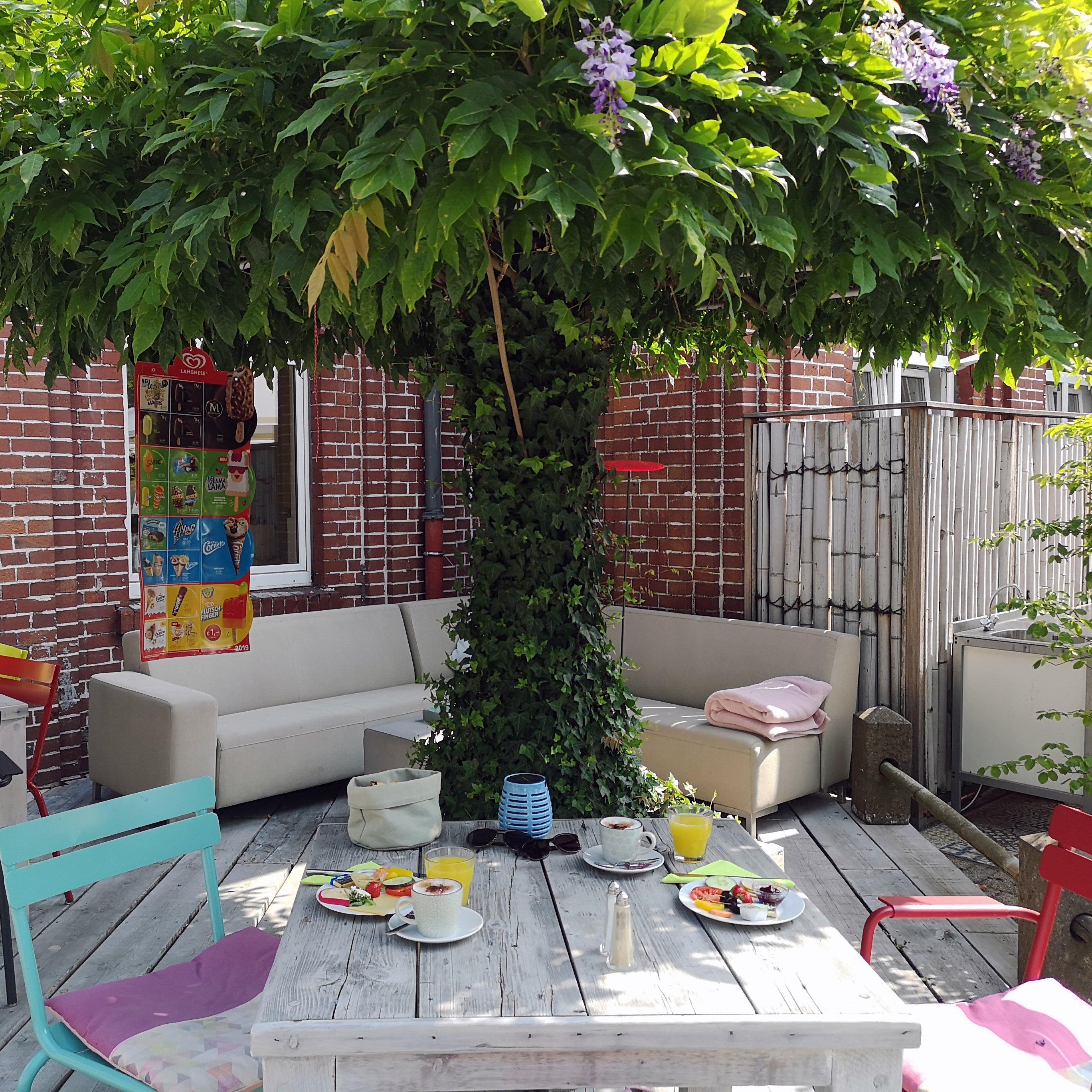 Das Bild zeigt den Innenhof des In Hostel Veritas mit Frühstückssituation
