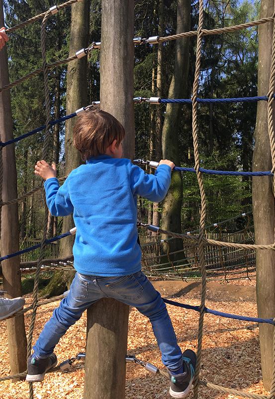 Das Bild zeigt einen kleinen Jungen beim Klettern im Kettelerhof in Haltern