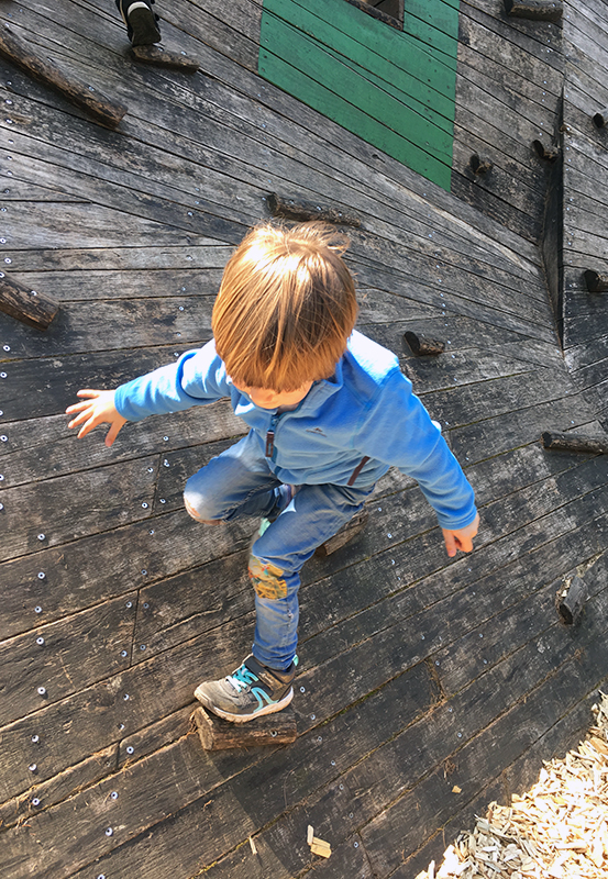 Das Bild zeigt einen kleinen Jungen beim Klettern an einer Holzwand im Kettelerhof in Haltern