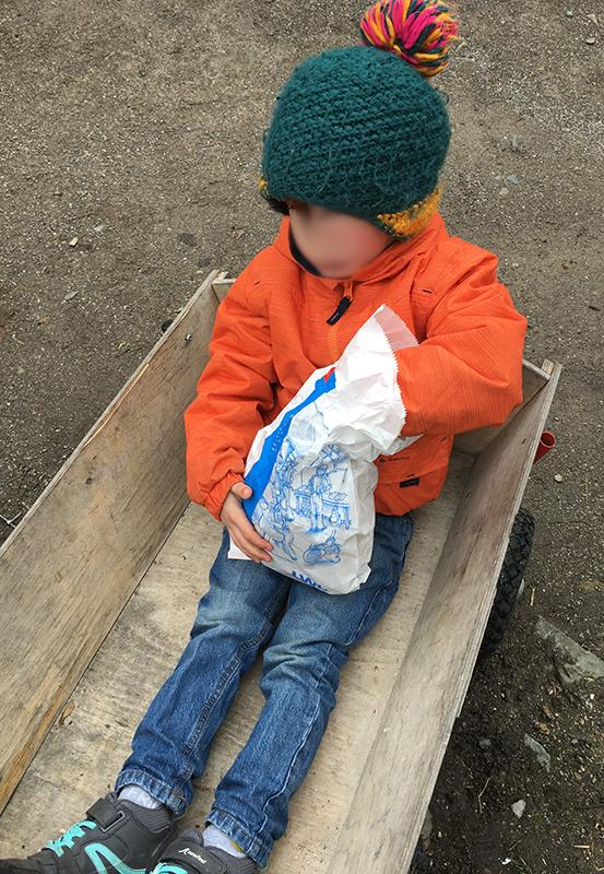 Das Foto zeigt einen kleinen Jungen beim Brotessen