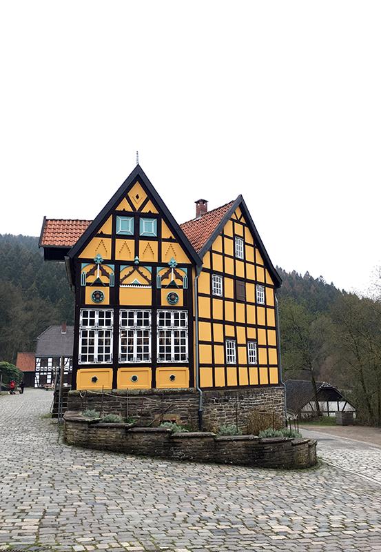 Das Bild zeigt ein gelbes Fachwerkhaus im LWL Freilichtmuseum Hagen