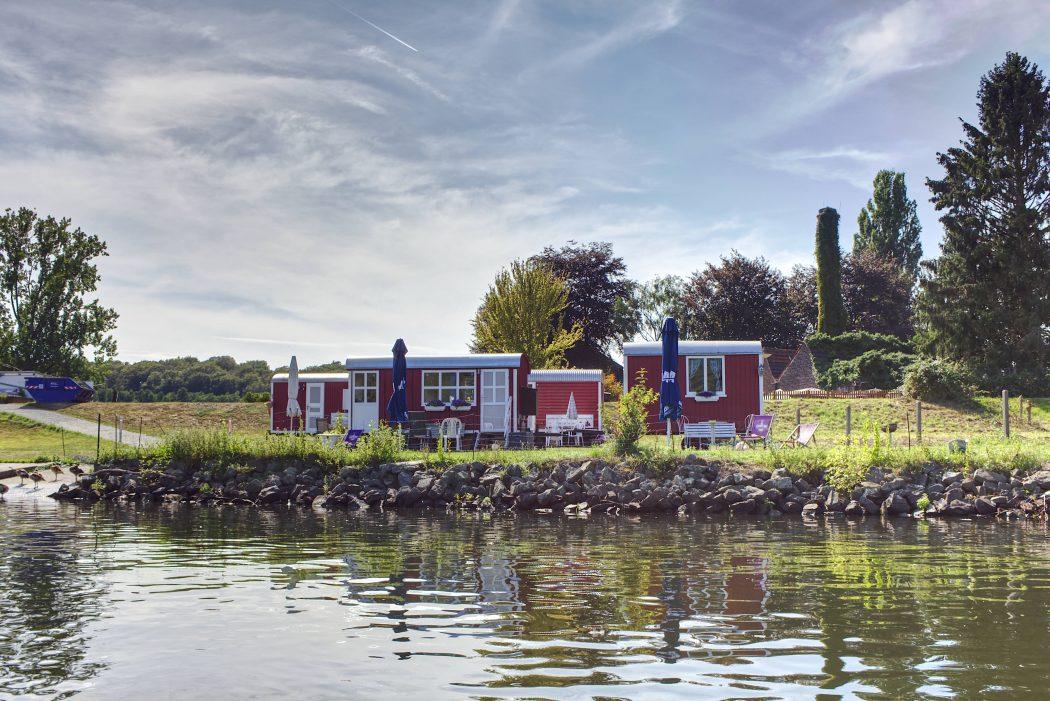 Das Foto zeigt die roten Bauwagen vom Bauwagenhotel Kanu-Kettwig an der Ruhr in Mülheim
