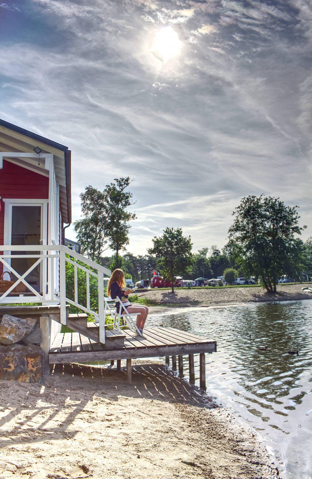 Das Foto zeigt eine Frau mit Buch vor einem Haus am See in der Dingdener Heide