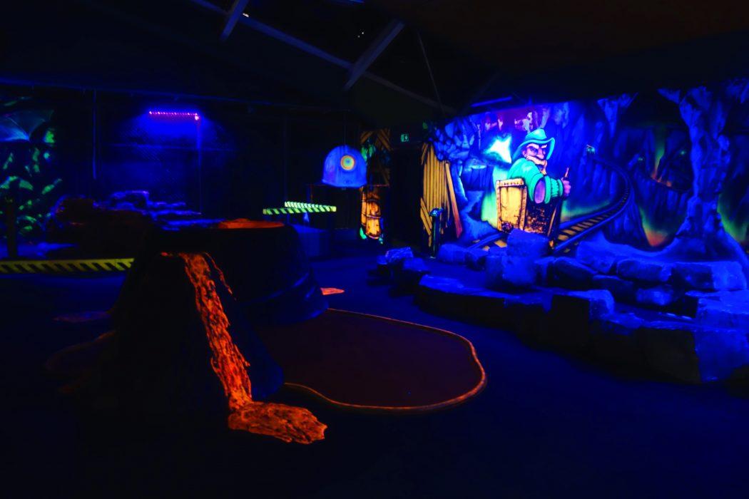 Das Bild zeigt die Minigolf-Anlaga im Alma Park im Schwarzlicht