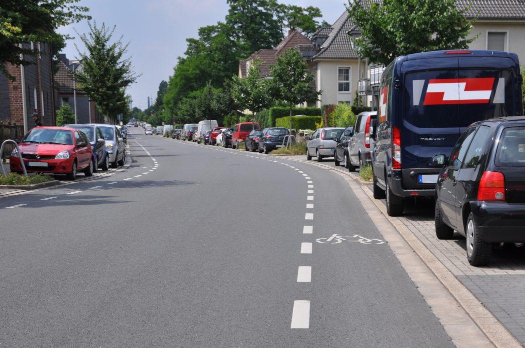 Das Foto zeigt einen schmalen Radweg auf einer Verkehrsstraße