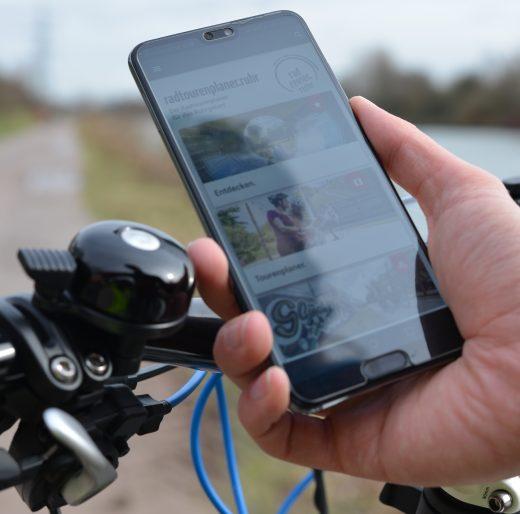 Das Foto zeigt ein Handy, auf dem der digitale radtourenplaner.ruhr angezeigt wird