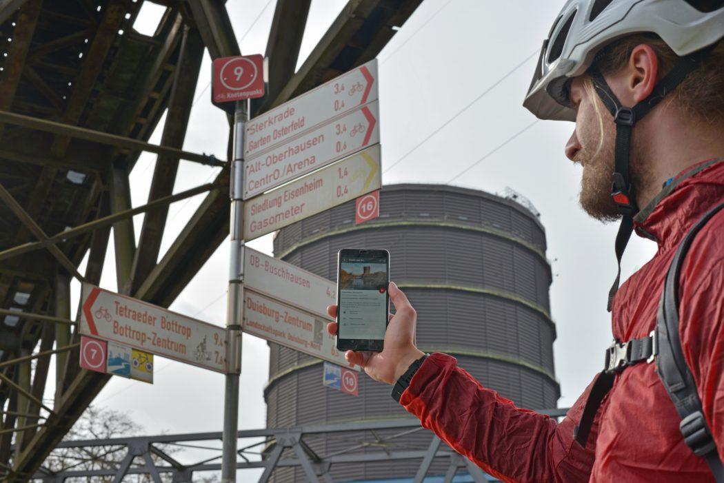 Das Foto zeigt einen Radfahrer vorm Gasometer Oberhausen, der den digitalen radtourenplaner.ruhr auf seinem Handy bedient