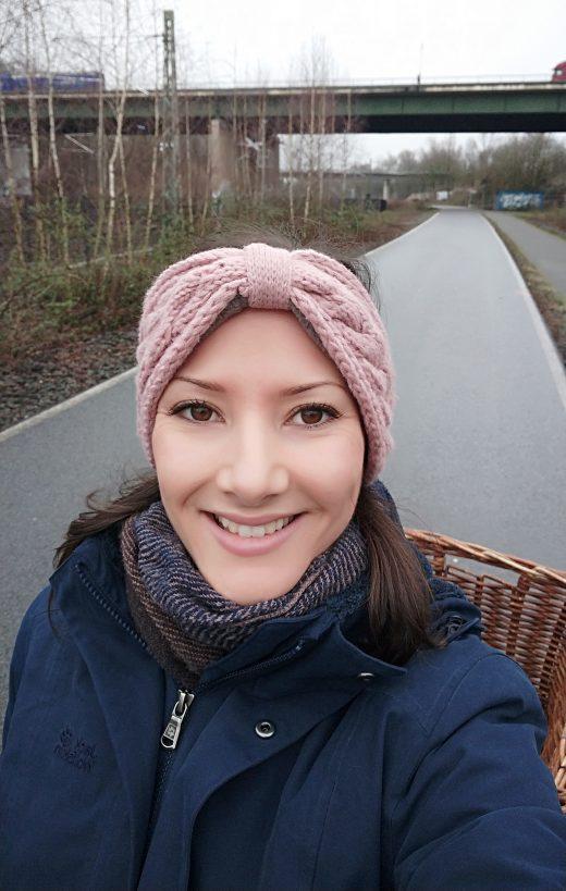 Das Foto zeigt Laura mit dem Fahrrad auf dem Weg zur Arbeit
