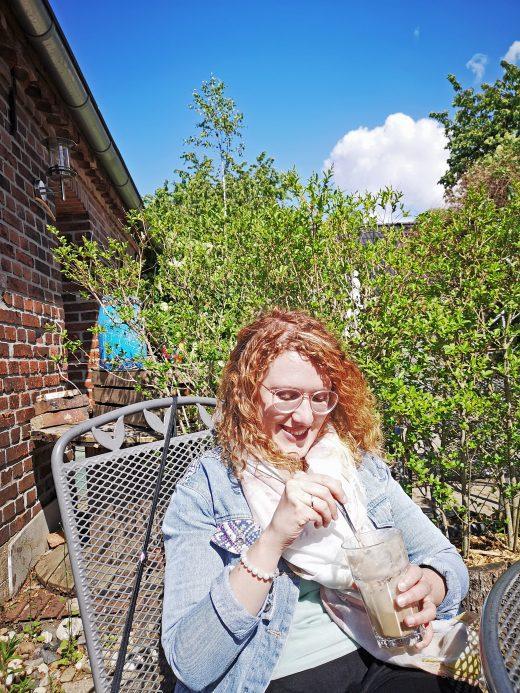 Das Bild zeigt die Autorin mit Kaffee.