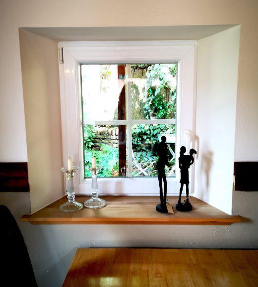 Das Bild zeigt Deko vor einem kleinen Fenster