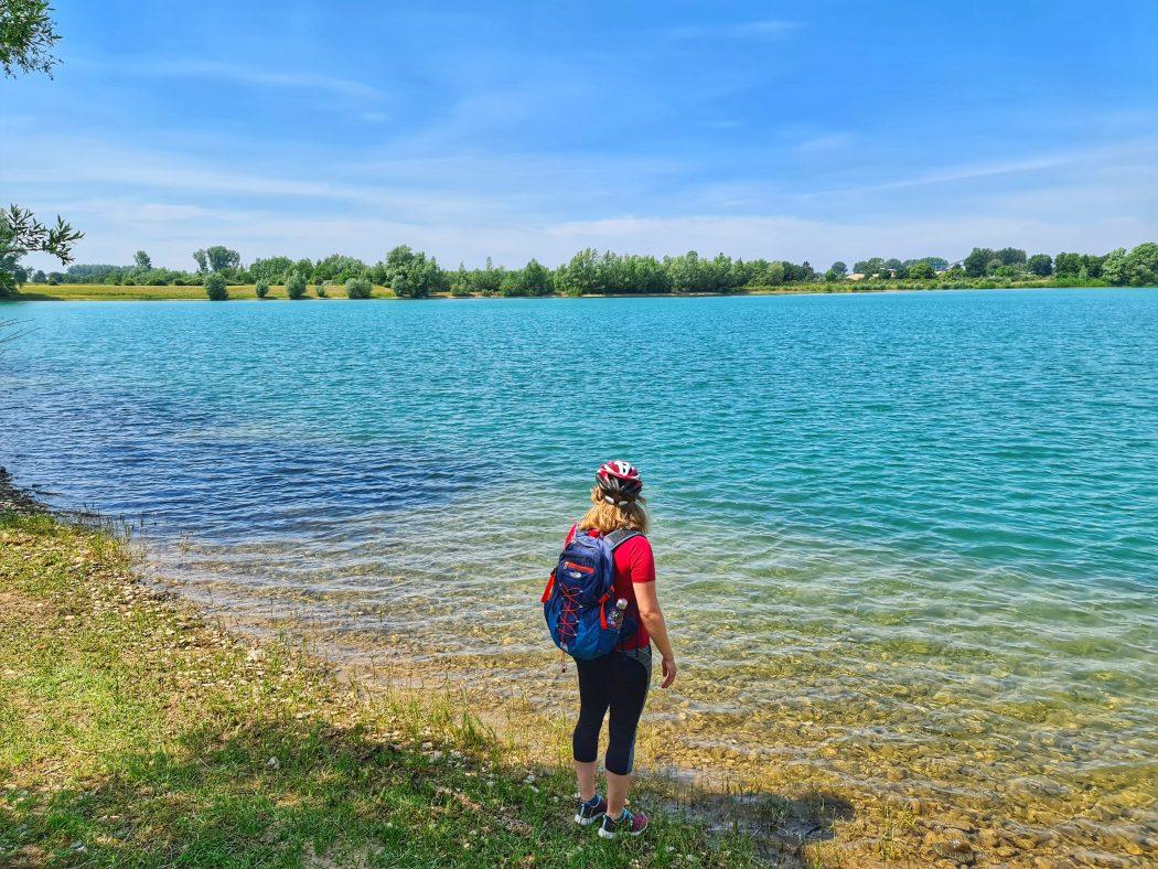 Das Foto zeigt eine Radfahrerin an einem Baggersee im Kreis Wesel