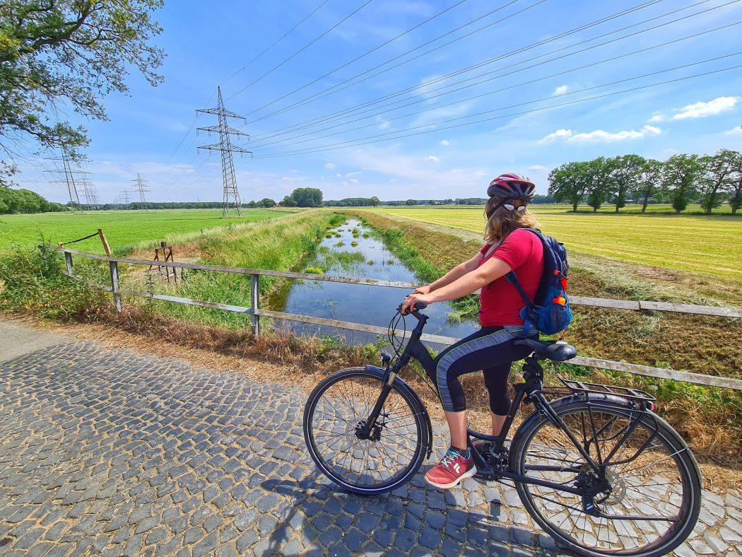 Das Foto zeigt eine Radfahrerin an der Issel im Kreis Wesel