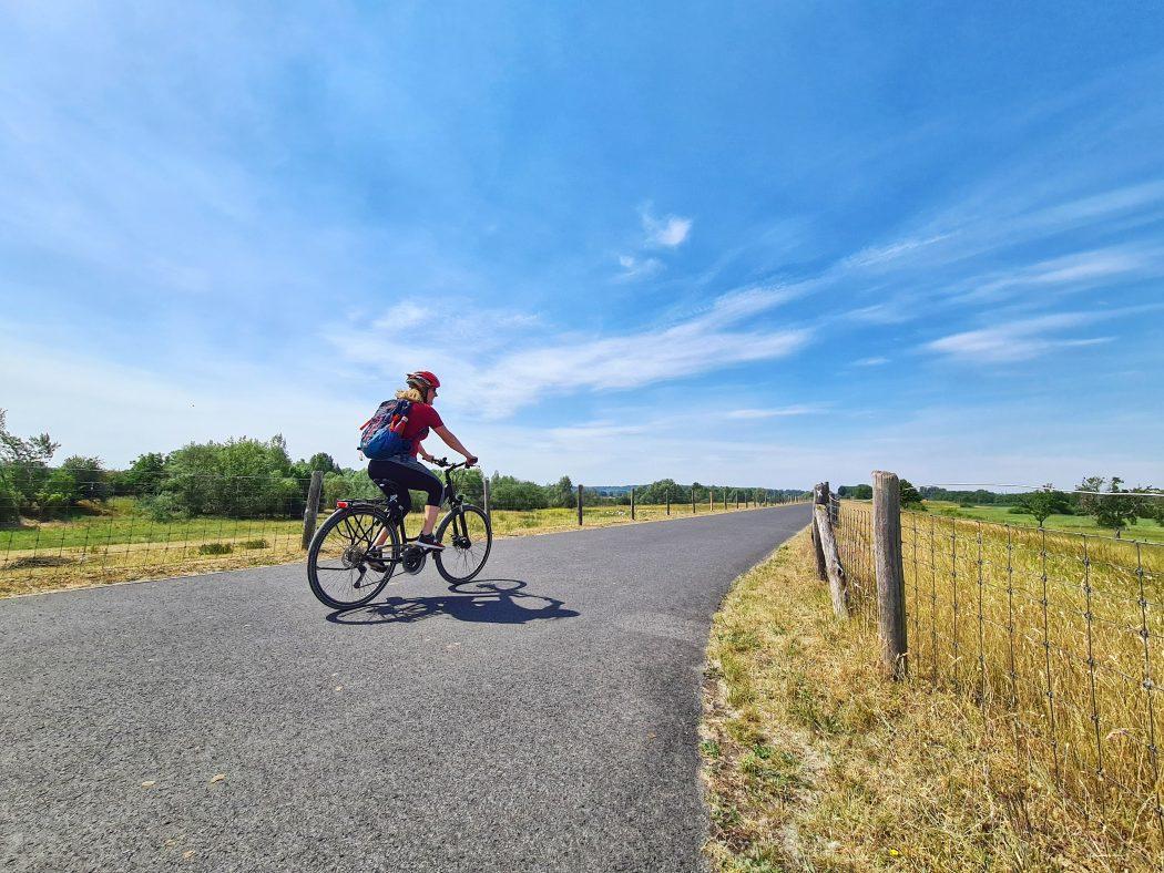 Das Foto zeigt eine Radfahrerin auf dem Deichradweg in Wesel