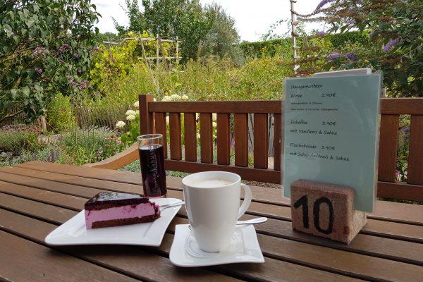 Das Foto zeigt Kaffee und Kuchen im idyllischen Garten des Hof Emscher-Mündung