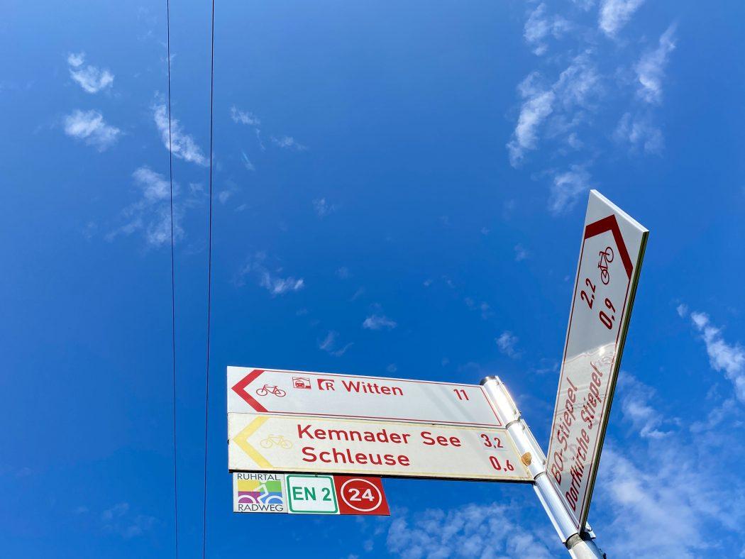 Das Foto zeigt ein Hinweisschild für Radfahrer samt Knotenpunkt und RuhrtalRadweg Einschub