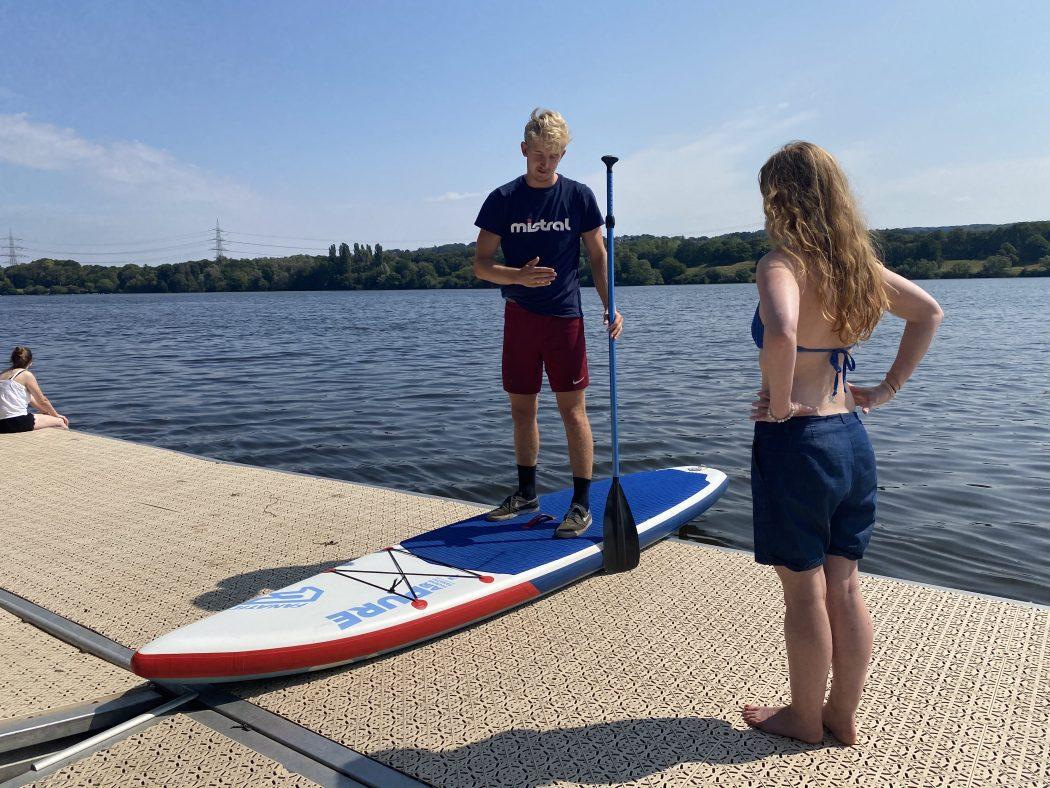 Das Foto zeigt Rebecca mit SUP-Profi Timo Kersting an der Surfschule Westufer am Kemnader See