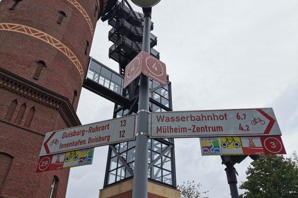 Das Foto zeigt einen Pfeilwegweiser mit RuhrtalRadweg-Logo