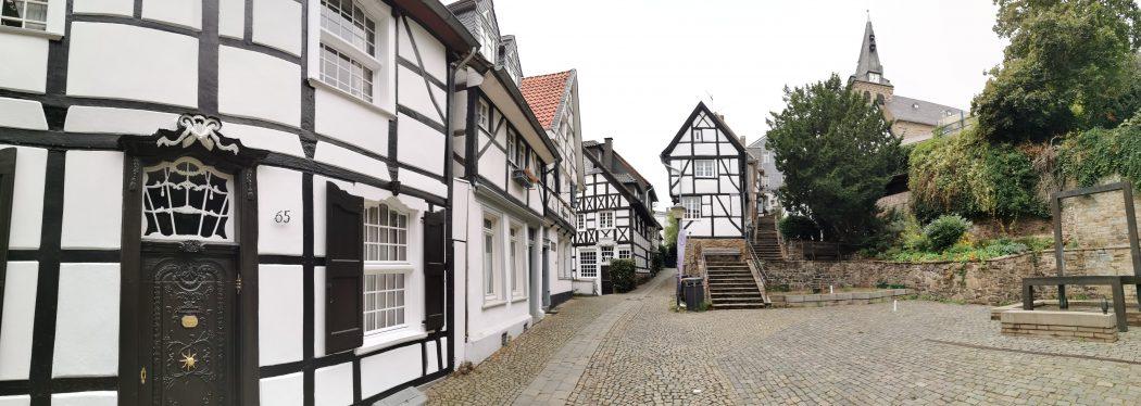 Das Foto zeigt traditionelle Fachwerkhäuser und eine moderne Brunneninstallation in Essen-Kettwig
