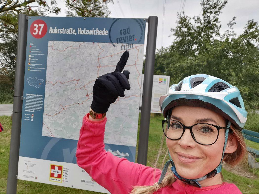 Das Foto zeigt Sandra an einer Knotenpunkttafel des radrevier.ruhr