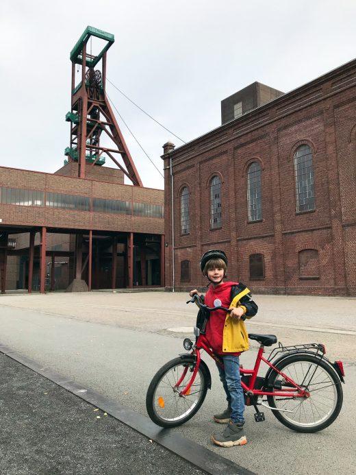 Das Foto zeigt ein Kind mit seinem Fahrrad auf dem Gelände der Zeche Zollverein in Essen