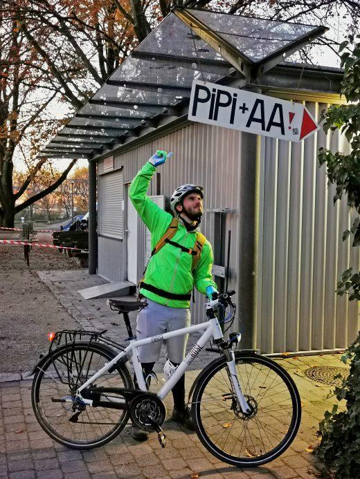 """Das Foto zeigt einen Radfahrer am Schild """"PIPI + AA"""" im Kaisergarten Oberhausen"""