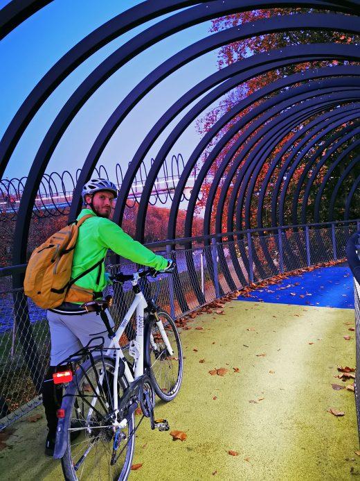 Das Foto zeigt einen Radfahrer auf der beleuchteten Brücke Slinky Springs to Fame in Oberhausen