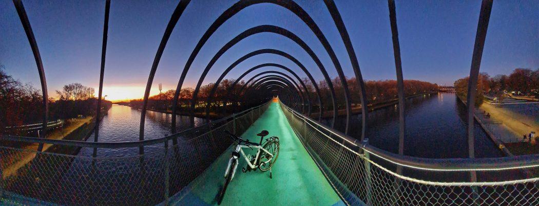 Das Foto zeigt ein Fahrrad auf der beleuchteten Brücke Slinky Springs to Fame in Oberhausen
