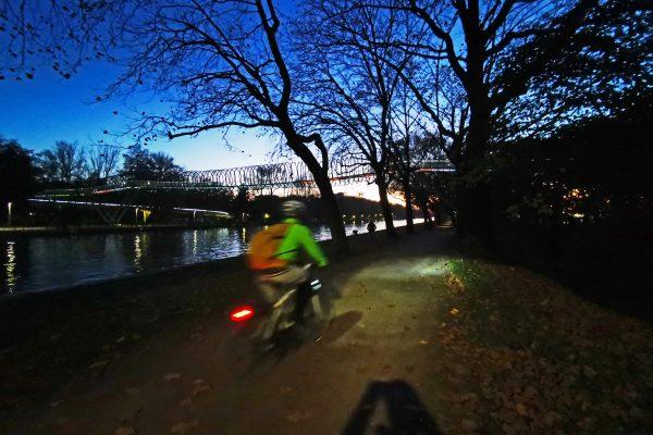 Das Foto zeigt einen Radfahrer im Dunkeln am Rhein-Herne-Kanal in Oberhausen