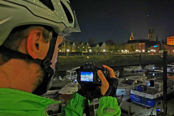 Das Foto zeigt einen Radfahrer beim Fotografieren im dunklen Innenhafen Duisburg