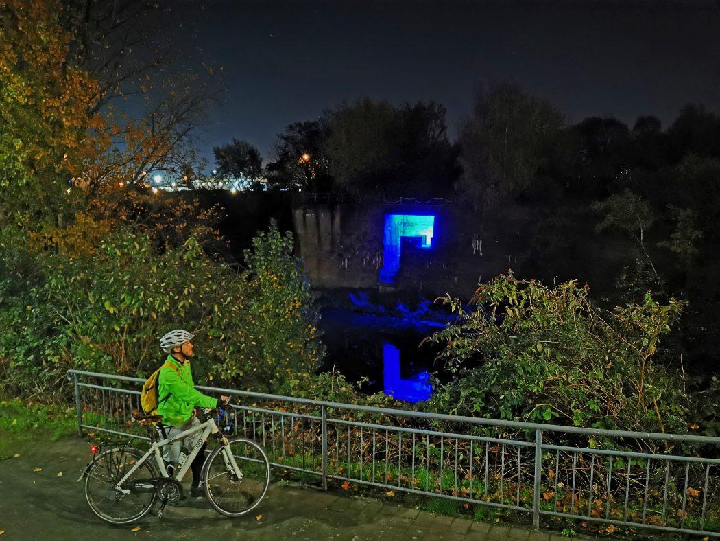 Das Foto zeigt einen Radfahrer in Dunkeln an der blauen Grotte in Duisburg