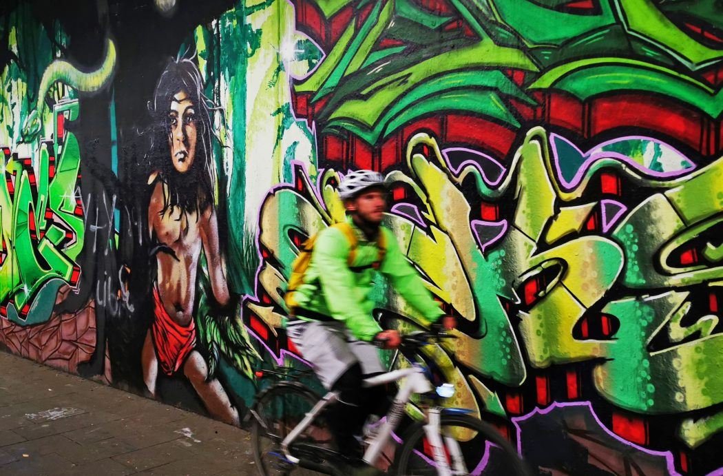Das Foto zeigt einen Radfahrer vor einer Graffitiwand in Duisburg