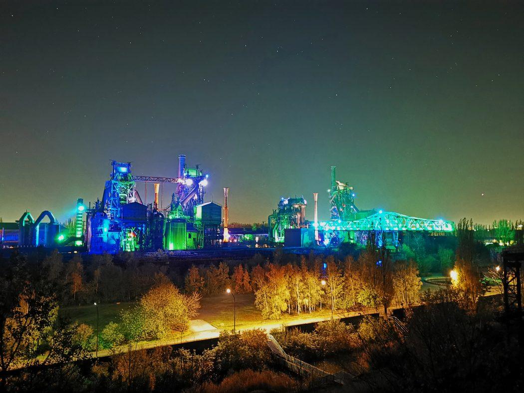 Das Foto zeigt den Sternenhimmel über dem beleuchteten Landschaftspark Duisburg-Nord
