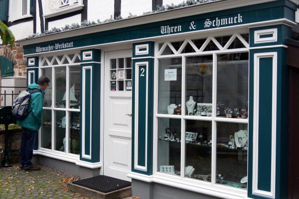 Das Foto zeigt einen Mann am Schaufenster der Uhrmacher-Werkstatt in der Altstadt von Mülheim an der Ruhr
