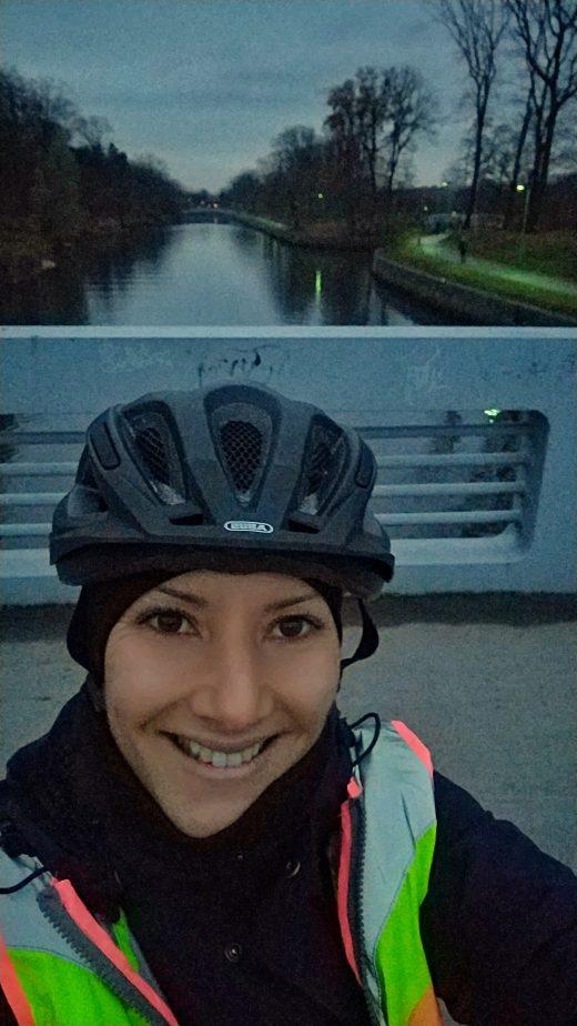 Das Bild zeigt eine Radfahrerin vor einem Kanal