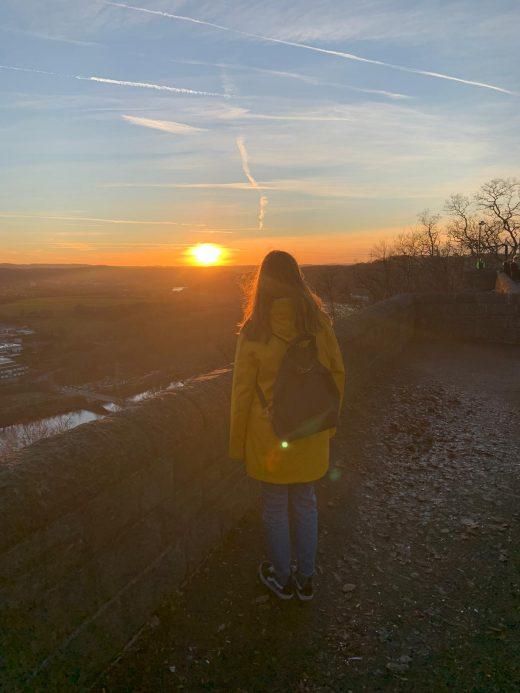 Das Bild zeigt eine Frau im Sonnenuntergang