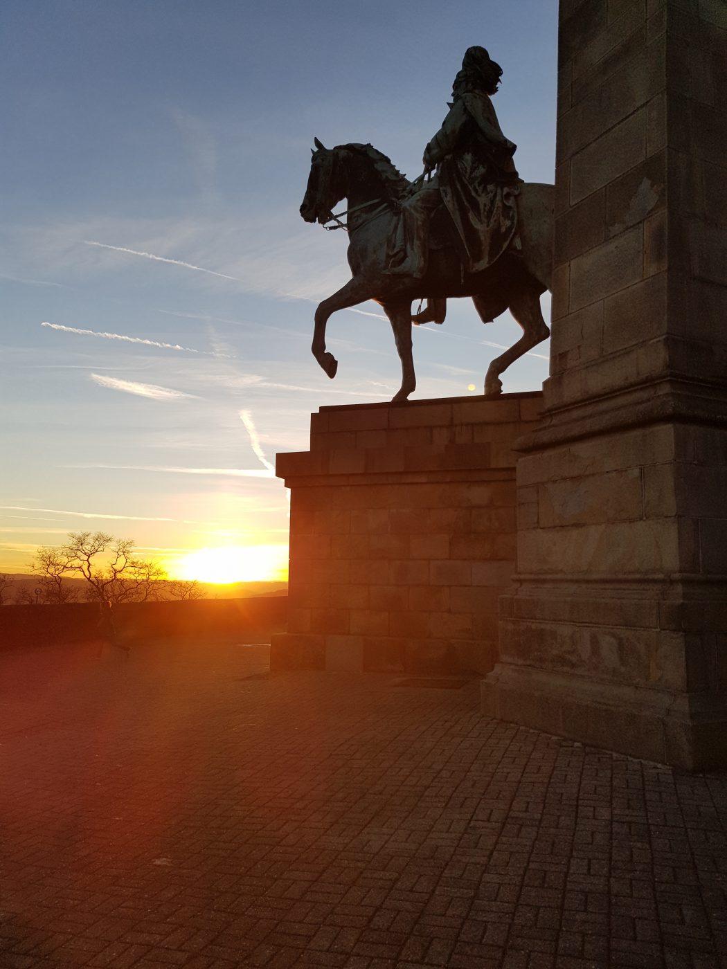 Das Bild zeigt eine Reiterstatue vor untergehender Sonne