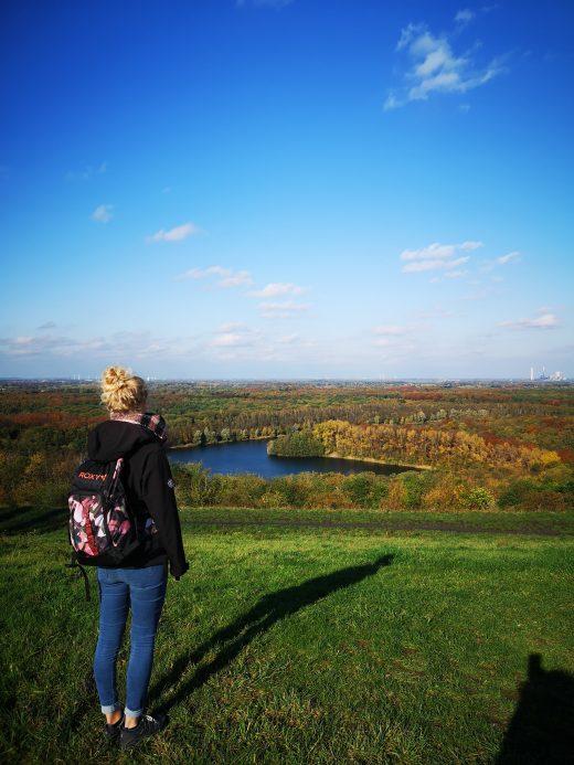Das Bild zeigt eine Frau von hinten mit Blick auf einen See