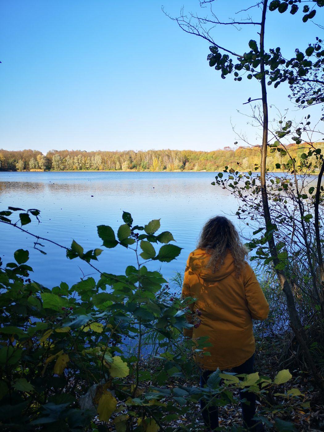 Das Bild zeigt eine Frau an einem See