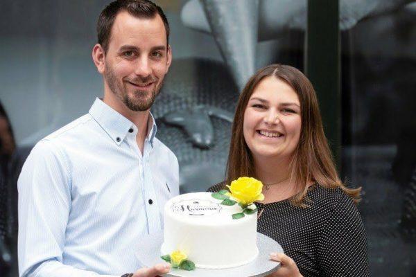 Das Foto zeigt die Inhaber der Confiserie Harmonie mit einer kleinen Torte
